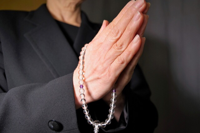 喪服で数珠をもって手を合わせる女性の画像