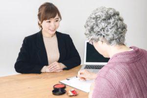 契約書に押印する高齢の女性