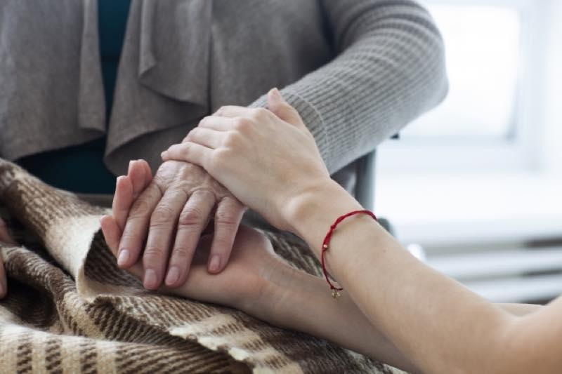 母の手を優しく握る娘