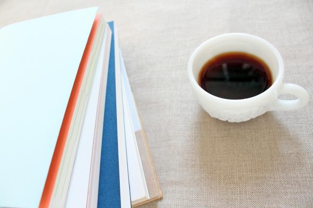 積まれた書籍とコーヒー