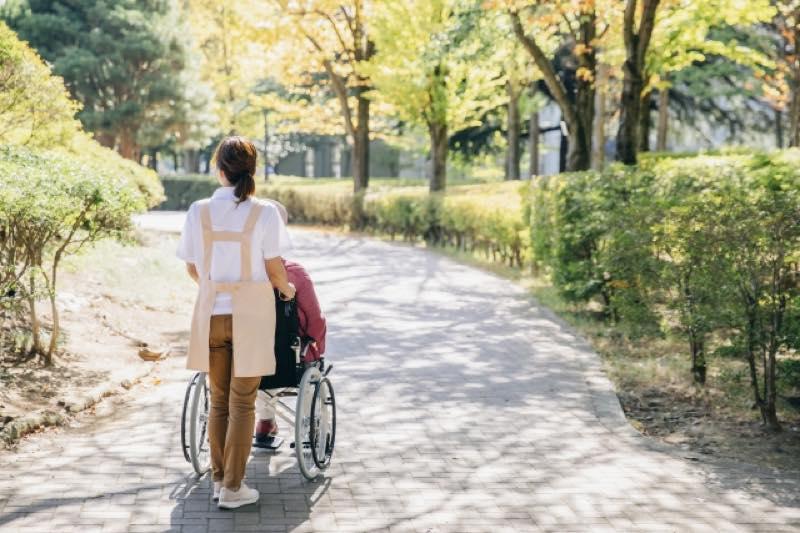 車椅子の女性と介護職員の後ろ姿