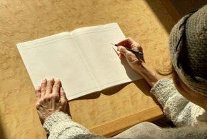 ノートに書く女性高齢者