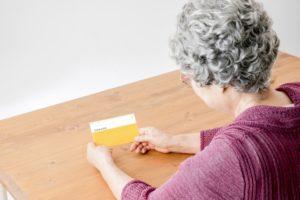 通帳を持つ女性高齢者