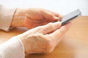 スマホを操作する高齢女性の手