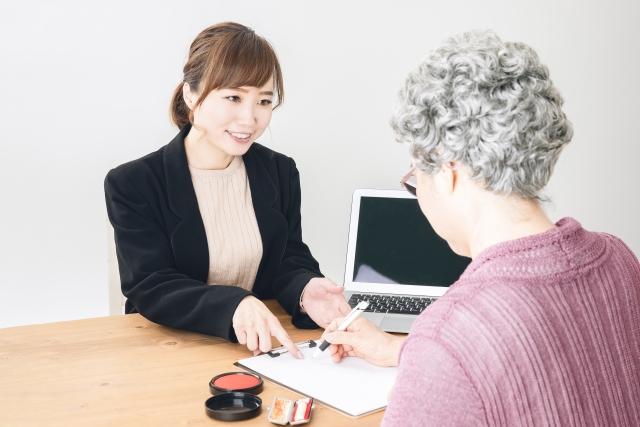 契約をする高齢女性