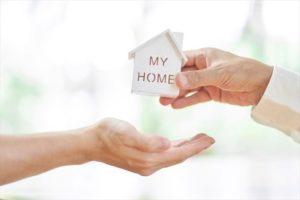 小さな家の模型を渡す手